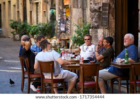 ROME, ITALY - AUGUST 10, 2013: Local men sitting outside a cafe terrace in the afternoon with coffee and soft drinks in the city center of Rome, Italy. #1717354444