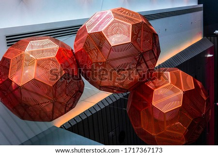 Colorful Picture who depicts 3 red polygons attached to each other suspended in the air.