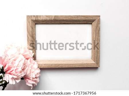 Wooden photo frame. Pink carnation. White background. Frame on a white background.