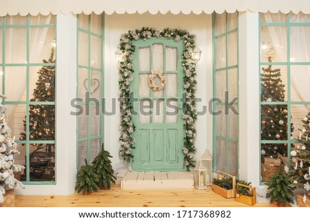 Porch with green door in Christmas decorations and Christmas trees. Spruce garlands around the door. Beautiful winter terrace of the house with garlands of retro light bulbs #1717368982