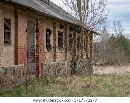 picture with an abandoned, old farm from collective farm times, early spring