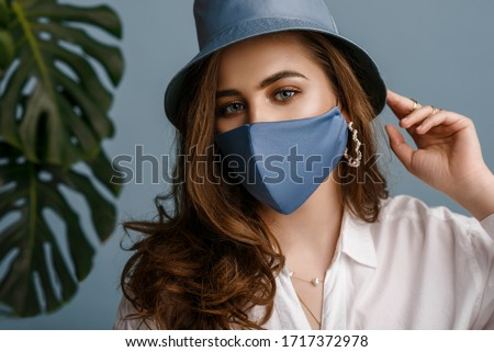 Woman wearing stylish outfit with luxury designer protective blue face mask, bucket hat, pearl earrings. Trendy Fashion accessory during quarantine of coronavirus pandemic. Close up studio portrait #1717372978