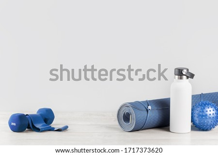 Rolled blue yoga mat and white metal water bottle flask grey wooden surface Dumbbell rubber resistance band. Gender neutral fitness and exercise concept and hydration with copy space. Active lifestyle #1717373620