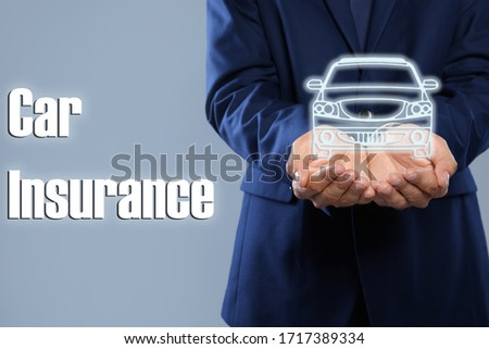 Man demonstrating image of auto on grey background, closeup. Car insurance