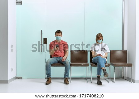 A guy and a girl in medical masks, sitting in a queue, and waiting for a doctor's appointment in the hospital. #1717408210