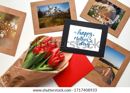 Red tulips bouquet among picture frames with photos about motherhood and Happy Mother's Day calligraphy greeting