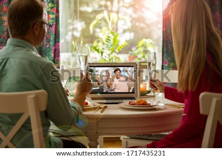 Man and woman sitting at the dining table, having dinner, drinking Champagne and having video call with senior parents on laptop. Staying home, quarantine and social distancing celebration of event.  #1717435231