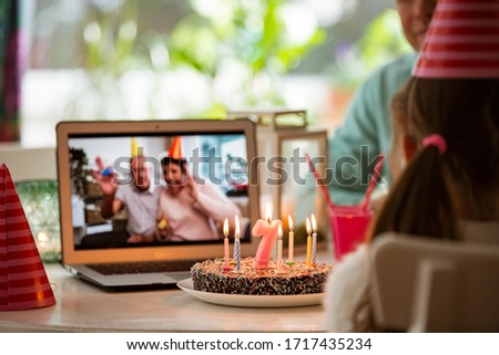 Happy little girl celebrating birthday at home with parents and grand parents on video call. Laptop with senior couple online, cake with candles on table. #1717435234