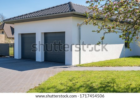 Modern and luxurious double garage with driveway and roller door Royalty-Free Stock Photo #1717454506