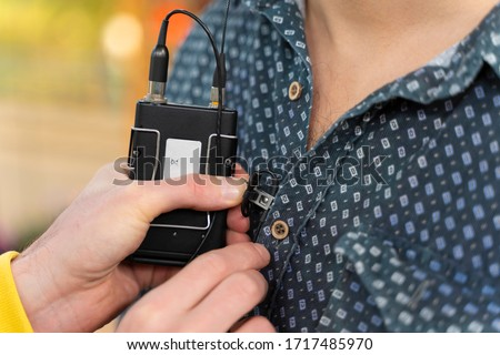 Behind the scene. Sound technician puts the lavalier microphone. Lav mic