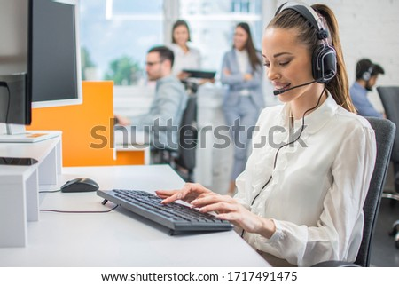 Portrait of female customer support or sales agent. Caller or receptionist phone operator working in call center. #1717491475