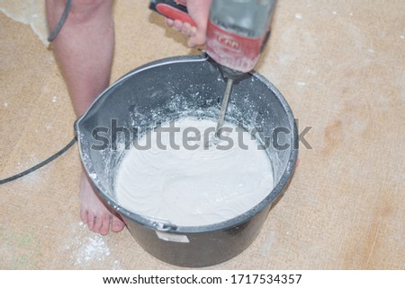 The builder stirs in a bucket a special mixture for repair #1717534357