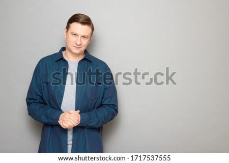Studio portrait of confident satisfied man wearing casual blue shirt, smiling slightly, holding hands folded together, listening or waiting somebody, standing over gray background, copy space on right #1717537555