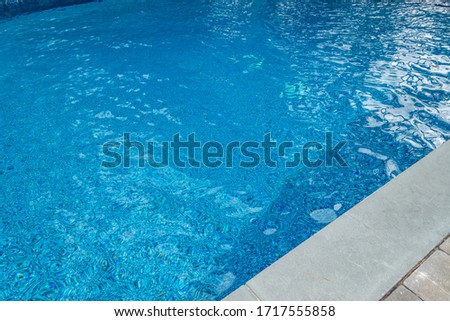 blue gound pool with wavy highlights and cement and brick circumference masonry  #1717555858