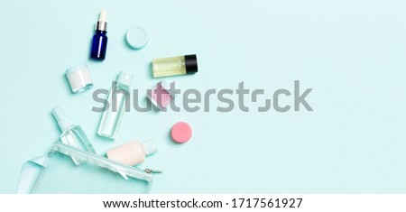 Group of small bottles for travelling on blue background. Copy space for your ideas. Flat lay composition of cosmetic products. Top view of cream containers with cotton pads. Royalty-Free Stock Photo #1717561927