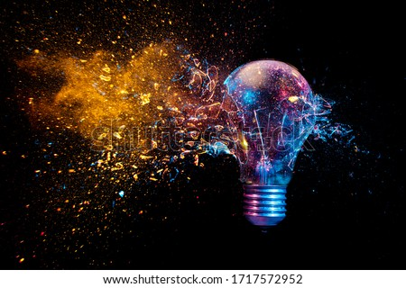 explosion of a traditional electric bulb. shot taken in high speed, at the exact moment of impact. Colored lights and black background. concept of creativity and fragility. Royalty-Free Stock Photo #1717572952