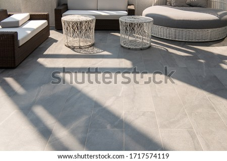 Outdoor terrace area with grey floor tile with sitting area #1717574119
