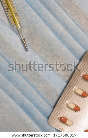 medical thermometer and tablets health care resources soft blue textile cloth background vertical format picture