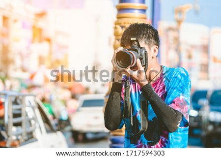 A young photographer in wet clothes use DSLR camera to take pictures of Songkran water splashing festival on the road in the city.