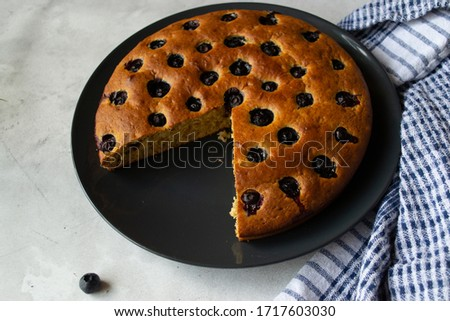 Banana pie with blueberries on a neutral grey plate. One blueberry on the front of the picture and a towel of white and blue on the left. Homemade pie.