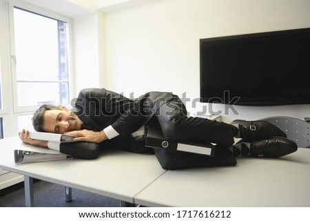 Exhausted businessman sleeping on desk #1717616212