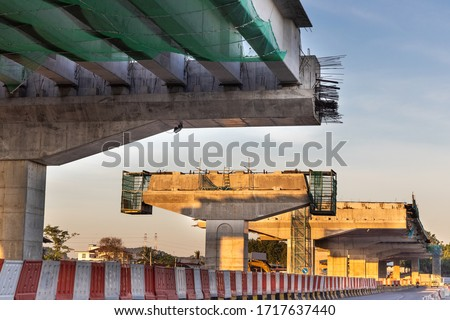 Construction of highway overpass bridge infrastructure in progress with morning sun rays in Malaysia Royalty-Free Stock Photo #1717637440