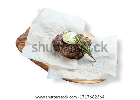 Beef steak minion with aromatic butter and a sprig of rosemary. Served on a wooden board and parchment.