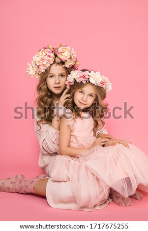 Photo of two beautiful girls with wreaths of flowers on their heads on a pink background, gentle hugs, touches. Family relations between sisters. Friendship and Love. Rapprochement. Child psychology