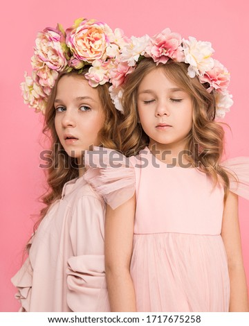 Studio photo of two beautiful girls with flowers in hair on a pink background. The baby closed eyes, sister is looking at the camera. Friendship and love. Rapprochement. Child and family psychology.