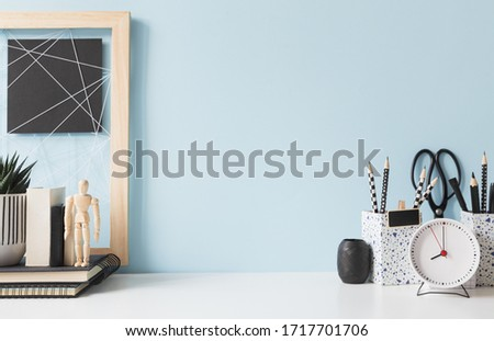 Home office creative desk with alarm clock, mannequin and blue wall. Royalty-Free Stock Photo #1717701706