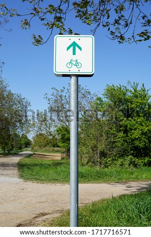 German green and white sign for a cycling trail. A square sign with a bike and an arrow at the side of a path with meadow, trees and blue cloudless sky. a bicycle symbol on a metal rod. #1717716571