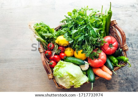 Vegetables in the basket organic vegetables on wooden background Royalty-Free Stock Photo #1717733974