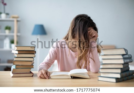Female student sits at a table with books preparing for exams. Education, home studying concept. #1717775074
