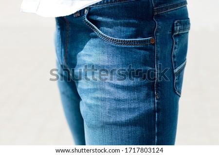 Detail closeup of men's blue denim trousers. #1717803124