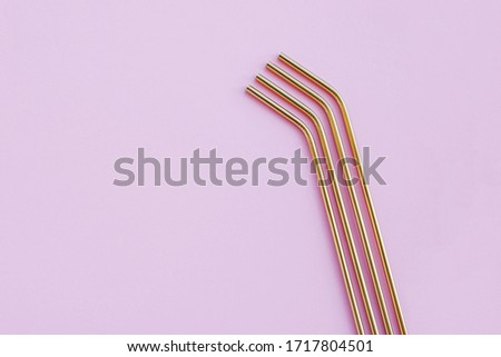 Stylish modern reusable eco-friendly golden metal straws on pastel pink background, close-up, high angle view. Space for text, flat-lay. Zero waste and sustainable lifestyle concept. #1717804501