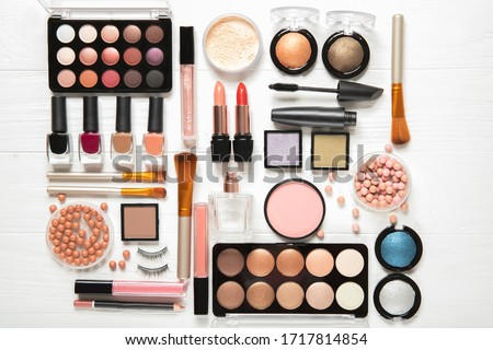 Decorative cosmetics and makeup brushes on a white background, top view #1717814854