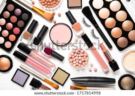Decorative cosmetics and makeup brushes on a white background, top view #1717814998