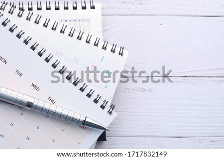 stack of calendar and pen on office desk