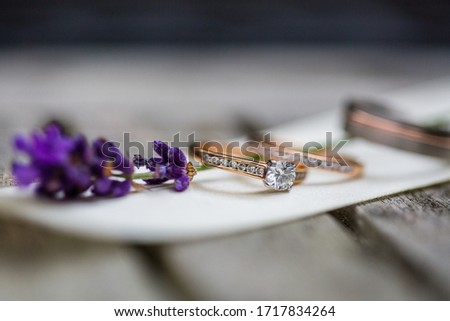Close up picture of the new beautiful diamond engagement ring and two golden wedding rings with round diamond placed on the cream ribbon,  purple lavender branch, grey wooden table on the background