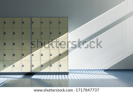 Lockers cabinets. Sunlight rays through the window on the changing room locker storage boxes, minimalist photography concept. Royalty-Free Stock Photo #1717847737