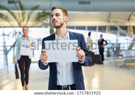 Business man at the airport holding a blank welcome sign as a service to the guest