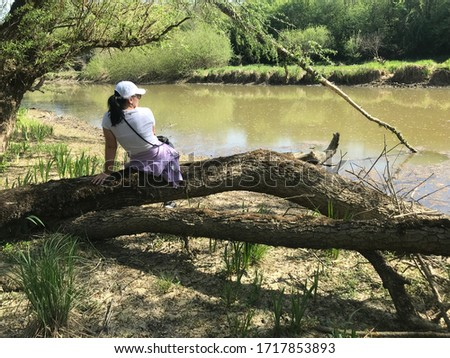 Woman sitting next to Odra river in Croatia Royalty-Free Stock Photo #1717853893