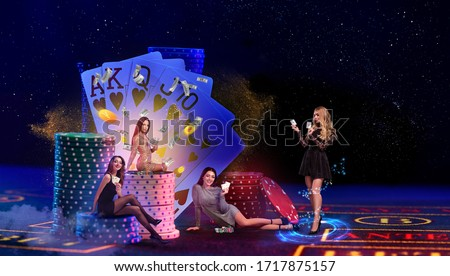 Women are showing aces and money. Posing on playing table with stacks of chips and playing cards on it, against blue background. Poker, casino Royalty-Free Stock Photo #1717875157