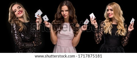 Three females in stylish dresses and jewelry. They are smiling, holding aces in their hands, posing on black background. Poker, casino. Close-up Royalty-Free Stock Photo #1717875181