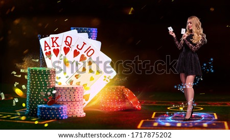 Girl holding two aces, smiling, posing on green playing table, next to stacks of chips and playing cards, flying dollars and coins. Poker, casino Royalty-Free Stock Photo #1717875202