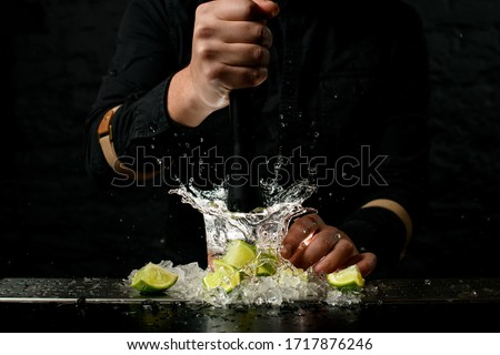 Close-up. Man bartender holds black madler in his hand and energetically squeeze slices of citrus to cocktail. Pieces of ice and lime at the bar. #1717876246