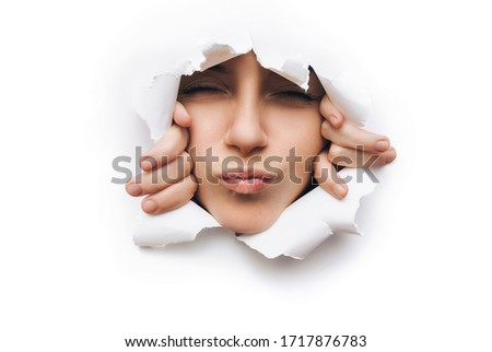 Portrait of a young caucasian woman with closed eyes and lips clenched for a kiss. He peeks through a torn hole in white paper, for harassment and intrusiveness of flirting. Isolated with copy space.