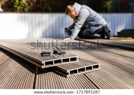 wpc terrace construction - worker installing wood plastic composite decking boards #1717895287