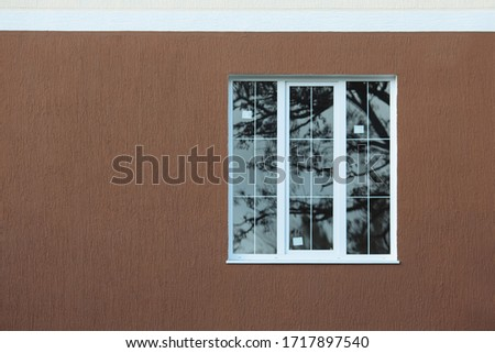 New large plastic window on three wings on facade with bark beetle texture after installation. Exterior of building. Picture is from front side.