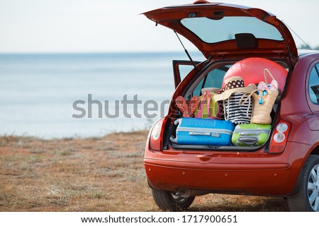 Suitcases and bags in trunk of car ready to depart for holidays. Moving boxes and suitcases in trunk of car, outdoors. trip, travel, sea. car on the beach with sea on background #1717900651